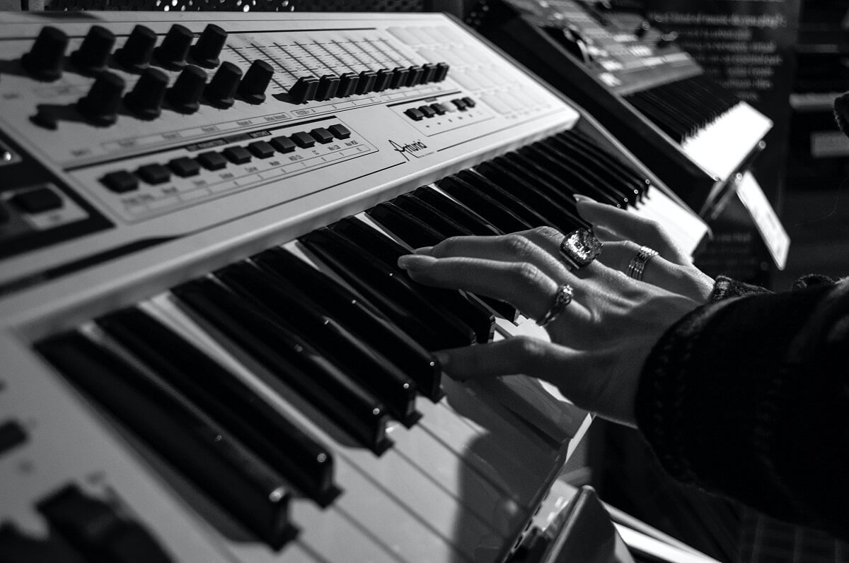 Picture of synthesizer keyboard with two hands playing keys