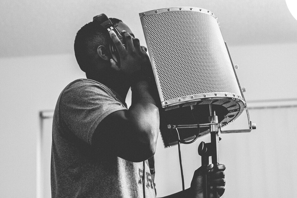 Man singing and recording vocals with headphones and vocal booth