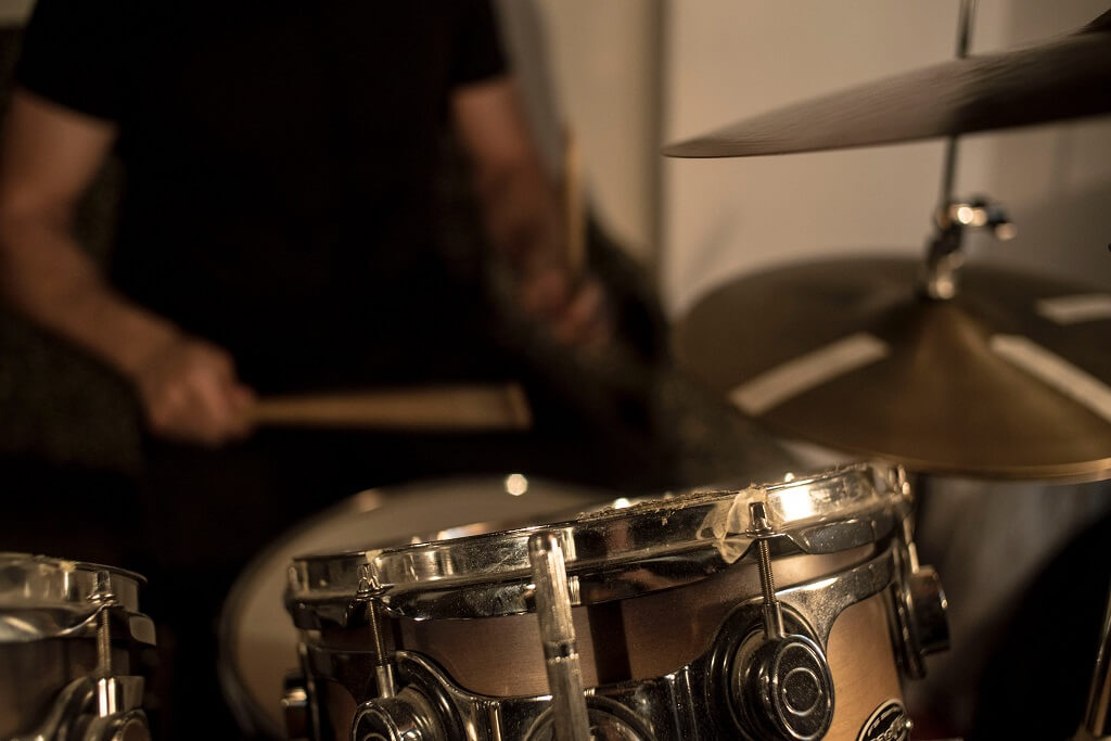 Drummer playing drum kit and cymbalswith two sticks