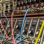 """Multi colored 1/4"""" jack patch leads pluggin into synthesizer"""