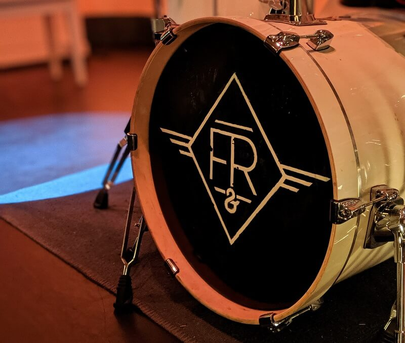 Image of White Bass Drum and drum set on stage