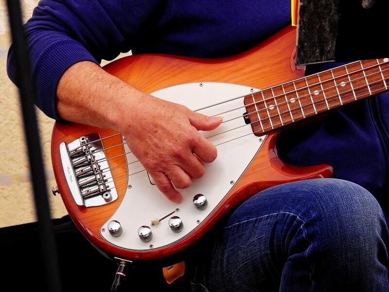 Man playing 5 string bass guitar slap bass