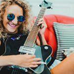 Youn woman playing black electric guitar