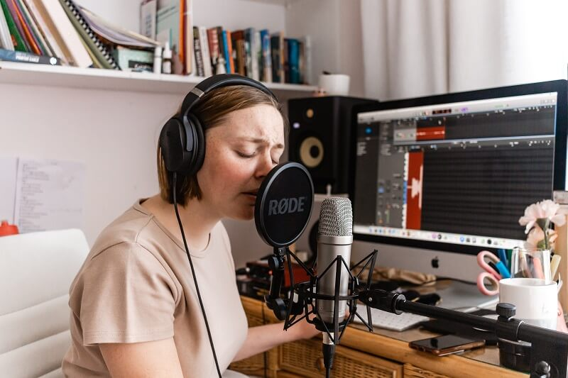 Woman singing into microphone with pop filter