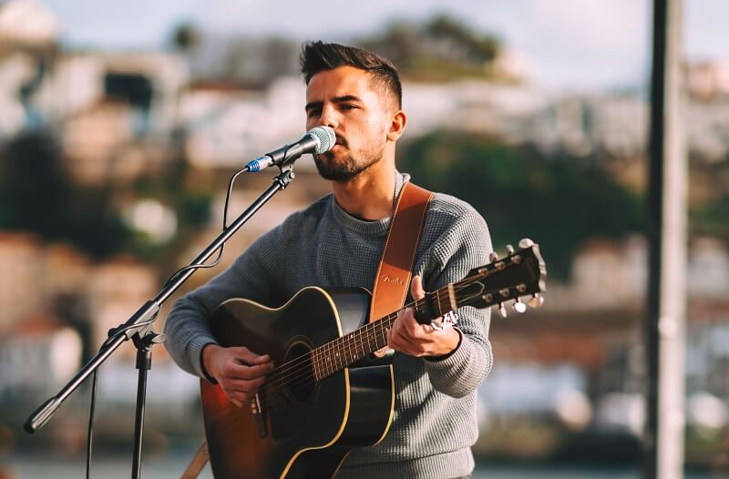 Young man playing guitar and singing busking outdoors